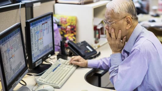 A stockbroker works in front of a screen displaying share prices at a securities brokerage in Hong Kong, China, on Wednesday, July 8, 2015.