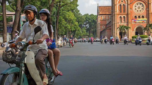 Motorists pass by the Saigon Notre-Dame Basilica in Ho Chi Minh City, Vietnam.