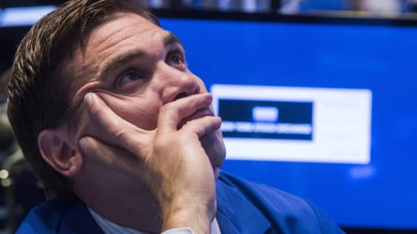 A trader waits for news while working on the floor of the New York Stock Exchange following a halt in trading in New York, July 8, 2015.