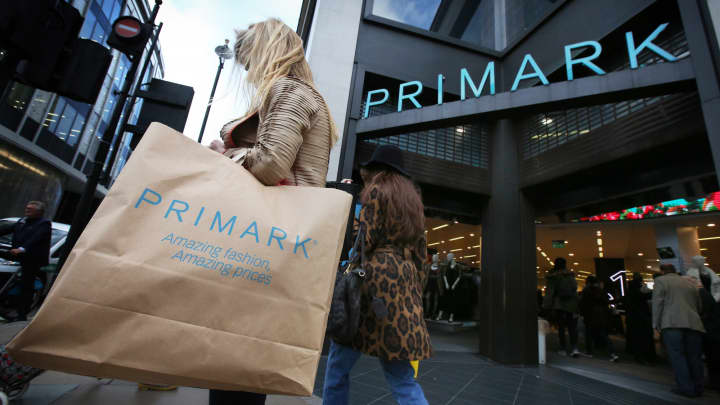 A customer walks with her purchases outside Primark's flagship store on Oxford Street in London.