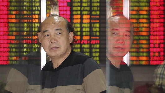 An investor is reflected on glass doors as he walks past in front of an electronic board showing stock information at a brokerage house in Shanghai.