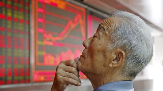 An investor watches an electronic board showing stock information at a brokerage office in Beijing, July 9, 2015. China shares rebounded sharply Thursday, with the Shanghai composite index posting its biggest percentage gain in six years.