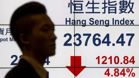 A man walks past a panel displaying the Hang Seng Index at the Hong Kong Exchanges, July 8, 2015.