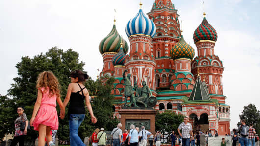 Tourists explore Red Square in front of St. Basil's Cathedral in Moscow.