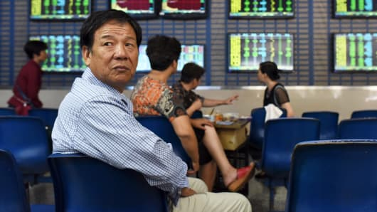 An investor sits in front of screens showing stock information, at a brokerage house in Hefei, China, July 8, 2015.