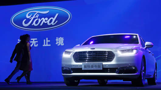 People walk near a Ford Taurus sedan displayed at a media event ahead of the 16th Shanghai International Automobile Industry Exhibition, April 18, 2015.