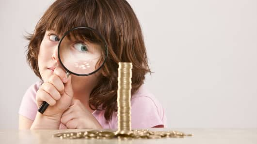 Young girl with magnifying glass and pile of coins