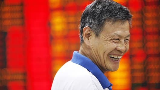 An investor smiles while observing the stock market at a stock exchange hall in Huaibei, China.