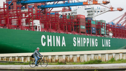 A man cycles past a container ship operated by China Shipping Container Lines.