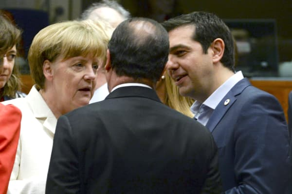 Greek Prime Minister Alexis Tsipras speaks with German Chancellor Angela Merkel (L) and French President Francois Hollande at a euro zone leaders summit in Brussels, Belgium, July 12, 2015.