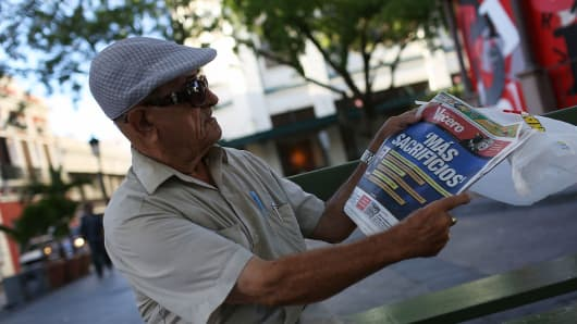 Tomas Colon reads a newspaper with a headline that reads, 'more sacrifices,' a day after the speech Puerto Rican Governor Alejandro Garcia Padilla gave regarding the government's $72 billion debt on June 30, 2015, in San Juan, Puerto Rico.