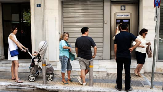 People wait in line to withdraw cash from an ATM machine in downtown Athens on July 9, 2015.