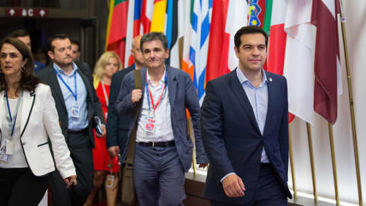 Alexis Tsipras, Greece's prime minister, right, and Euclid Tsakalotos, Greece's finance minister, center, depart following all-night bailout talks in Brussels, Belgium, on Monday, July 13, 2015.