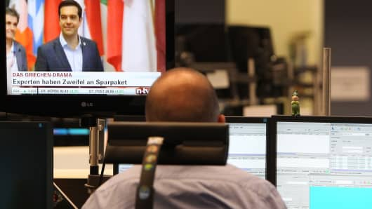 A trader works as one of his screens displays Greek Prime Minister Alexis Tsipras and news on the Greek debt crisis at the stock exchange in Frankfurt am Main, Germany, on July 13, 2015.