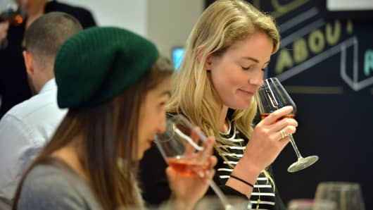 Elissa Garza, 25, of Boston, and Gabi Parsons, 24, of San Francisco (from left) sampled glasses of wine during a recent class that paired finance education with a wine tasting at the Society of Grownups, a financial education operation that uses a coffee shop and dinner club atmosphere to help attract millennials.