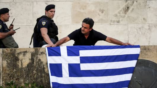 An anti-EU protester unfurls a Greek national flag next to riot police on the steps in front of the parliament building during a demonstration of about five hundred people in Athens, Greece July 13, 2015.