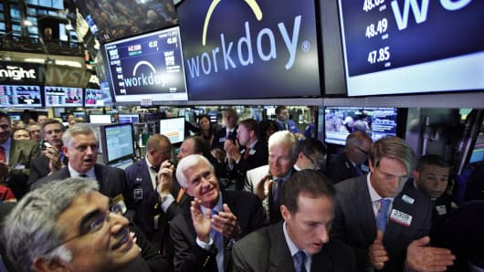 Workday co-founders and co-CEOs Aneel Bhusri (left) and Dave Duffield (center) applaud their company's first trade after their IPO at the New York Stock Exchange on Oct. 12, 2012.