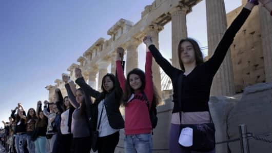 Schoolchildren form a human chain around the ancient Parthenon temple at the Acropolis in Athens.