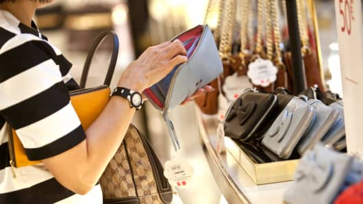 A customer looks at discounted hand bags and purses for sale in the Galeries Lafayette SA luxury department store in Paris.