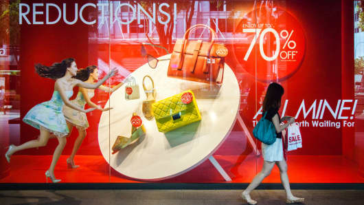 A shopper walks past a window display advertising sales at a Robinsons department store on Orchard Road in Singapore.