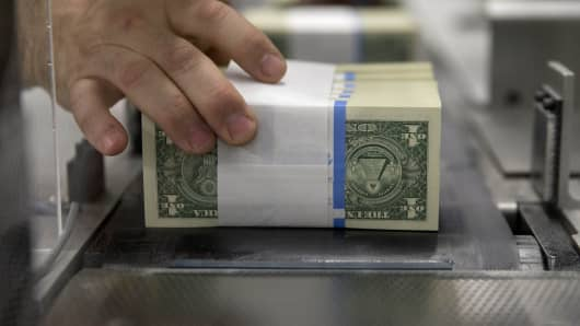 Banded one dollar notes are handled while traveling through a large examining packaging equipment machine at the U.S. Bureau of Engraving and Printing in Washington, D.C., U.S., on Tuesday, April 14, 2015.