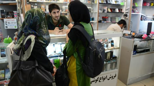 Two veiled women look at smart phone brands in Paytakht computer mall in Tehran, Iran.