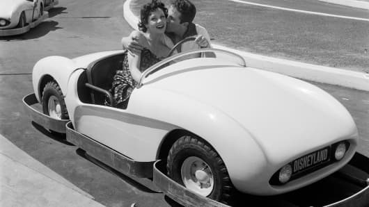 Actor Steve Rowland and actress Kathleen Case pose as they ride on Autopia during the opening day of Disneyland in Anaheim, California.