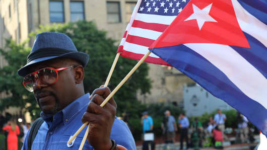 A man holds a Cuban and an American flag outside the Cuban embassy in Washington, D.C. as the two countries restore diplomatic relations after five decades.