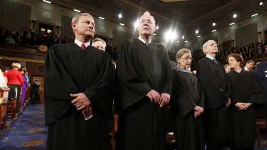 U.S. Supreme Court Chief Justice John Roberts, from left, stands with fellow justices Anthony Kennedy, Ruth Bader Ginsburg, Stephen Breyer and Elena Kagan.
