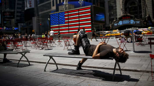 A man takes a nap during a sunny day at Times Square in New York.