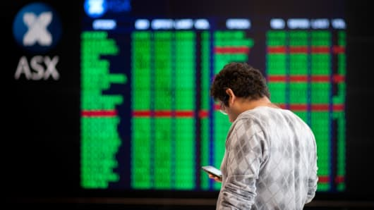 A man uses his mobile phone in front of electronic stock boards at the Australian Securities Exchange headquarters in Sydney, Australia.