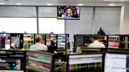 An employee watches a news broadcast on the trading floor at Panmure Gordon & Co. in London, U.K.
