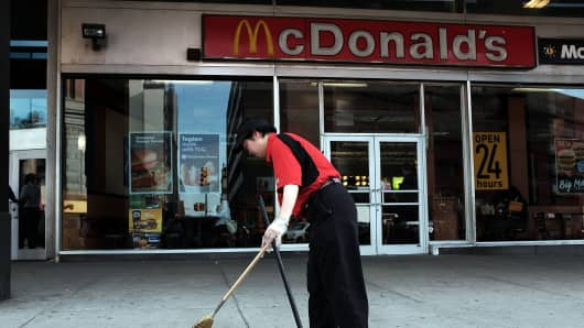 A McDonald's employee sweeps up in front of a restaurant on the morning when thousands of people took to the street to demand a minimum wage of $15 an hour on April 15, 2015 in the Brooklyn borough of New York City.