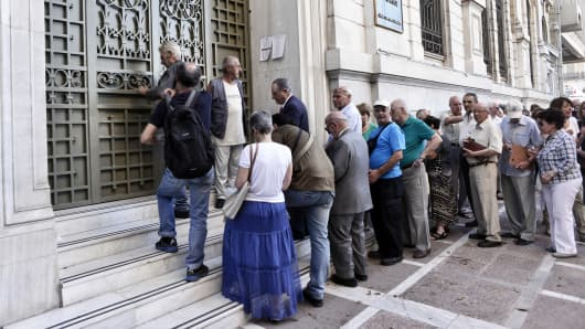 People wait to enter a bank branch as Greek banks reopened on Monday morning after three weeks of closure on July 20, 2015 in Athens, Greece.