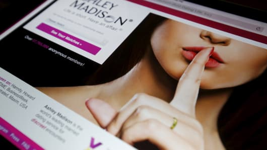 The homepage of the Ashley Madison website is displayed on an iPad.