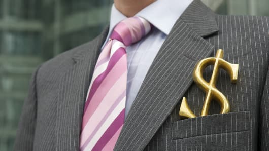 Businessman with golden dollar in suit pocket
