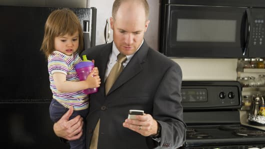 Businessman in kitchen holding toddler