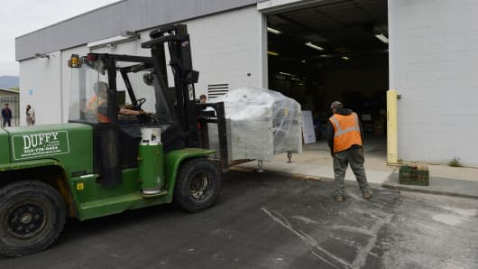 Workers move in a pick and place machine into the new Modular Robotics factory in Boulder, Colorado.