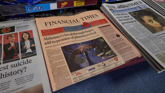 A copy of the Financial Times newspaper is seen alongside other British newspapers displayed for sale in a newsagents in London on July 23, 2015.