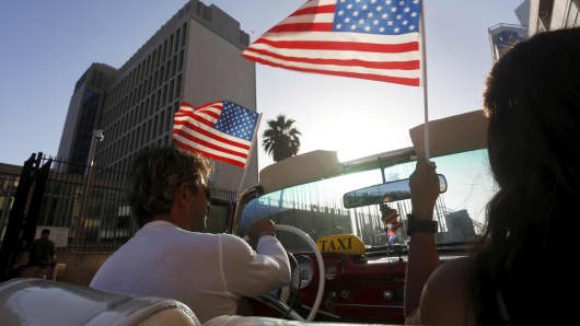 Cuban citizen Armando (L) and U.S tourist Lisa Fragoso wave U.S flag while passing the U.S. Interests Section, in Havana July 20, 2015.