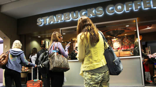 People wait in line at a Starbucks location.