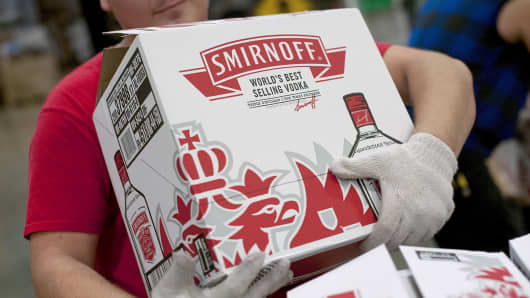 An employee reaches for a case of Diageo's Smirnoff brand vodka at a distribution warehouse in Bolingbrook, Ill.