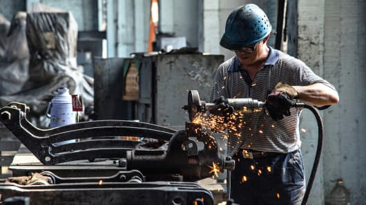 A worker repairs steam locomotive parts in Fuxin coal mine locomotive repair plant in Fuxin, China.