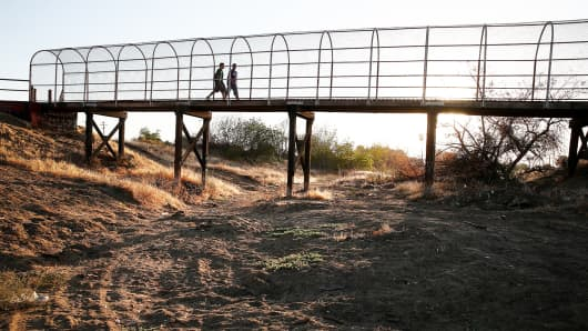A footbridge spans a completely dry river bed in Porterville, Calif.
