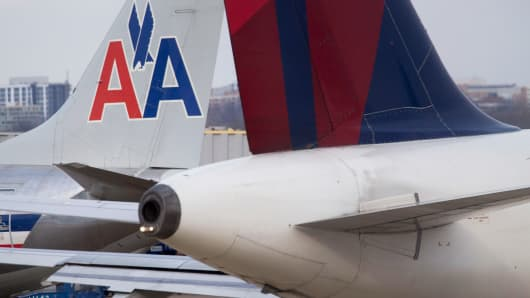 An American Airlines Group Inc. plane is seen past the tail of a Delta Air Lines Inc. jet at Ronald Reagan National Airport (DCA) in Washington, D.C.