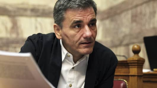 Greek Finance Minister Euclid Tsakalotos holds a draft of a reform bill at a parliamentary session in Athens, July 22, 2015.