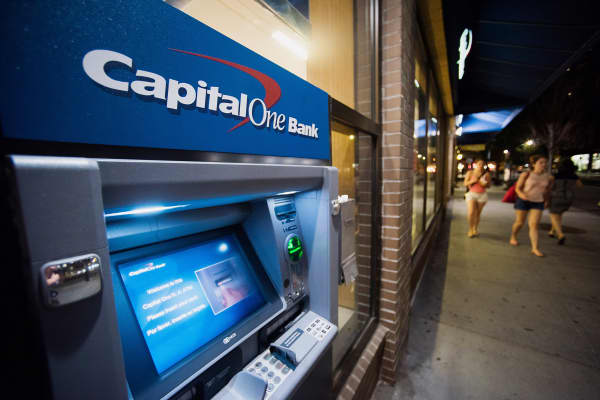 Pedestrians walk past a Capital One ATM outside of a bank branch in New York.