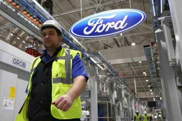 An employee walks past a Ford logo at a Ford factory in Dagenham, England.