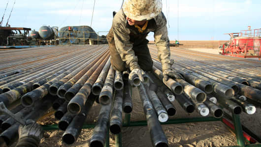 An oil rigger at a Schlumberger field prepares pipes in Midland, Texas.