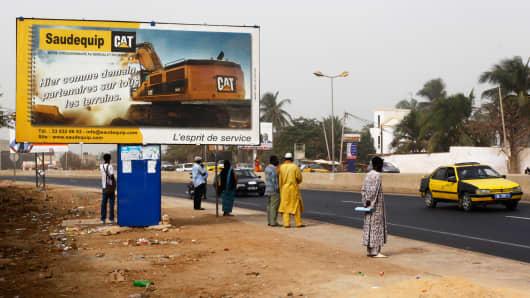 Pedestrians wait at a roadside beside a sign advertising Caterpillar heavy construction machinery in Dakar, Senegal, last January.